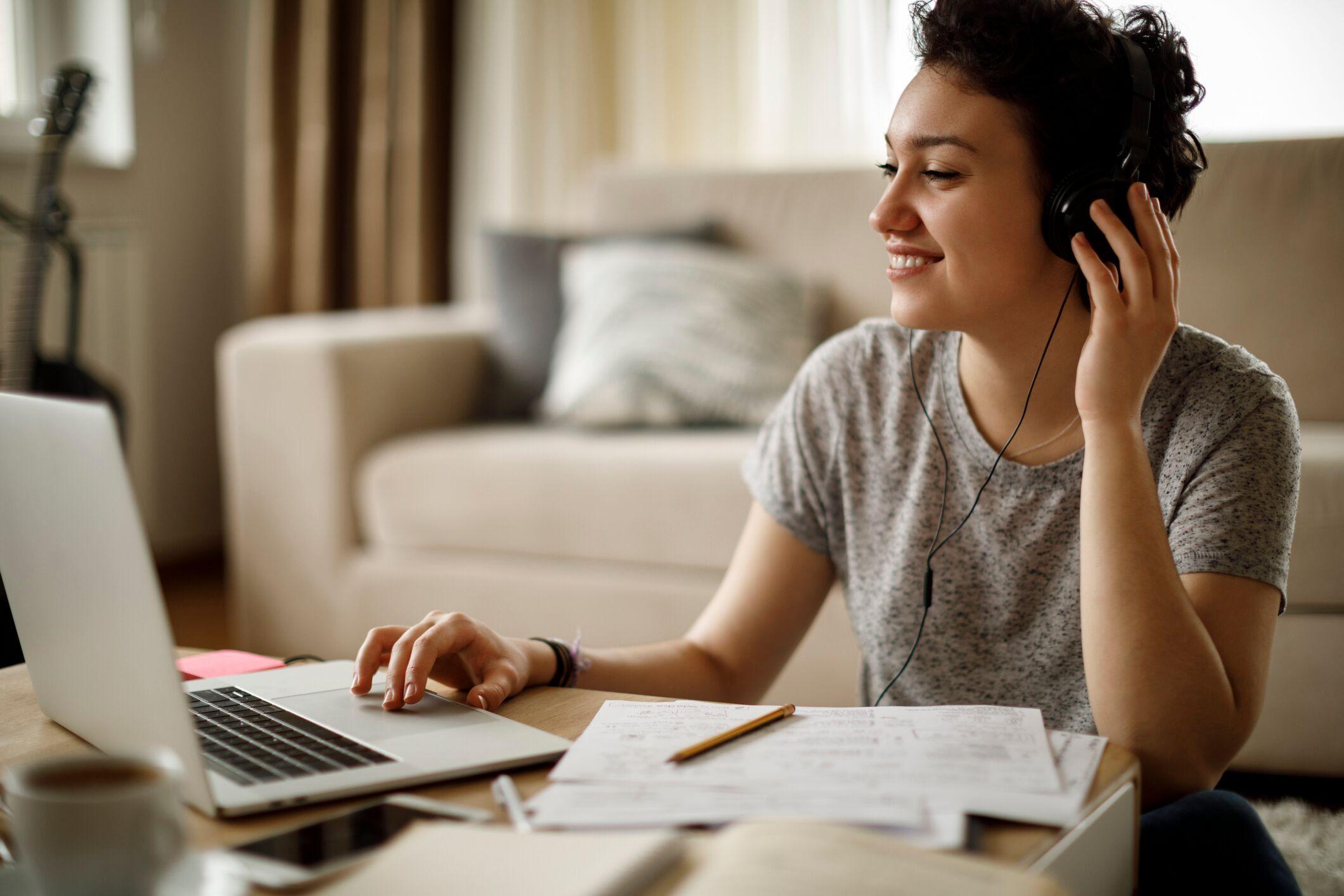 Kvinna som sitter framför sin dator med hörlurar på.
