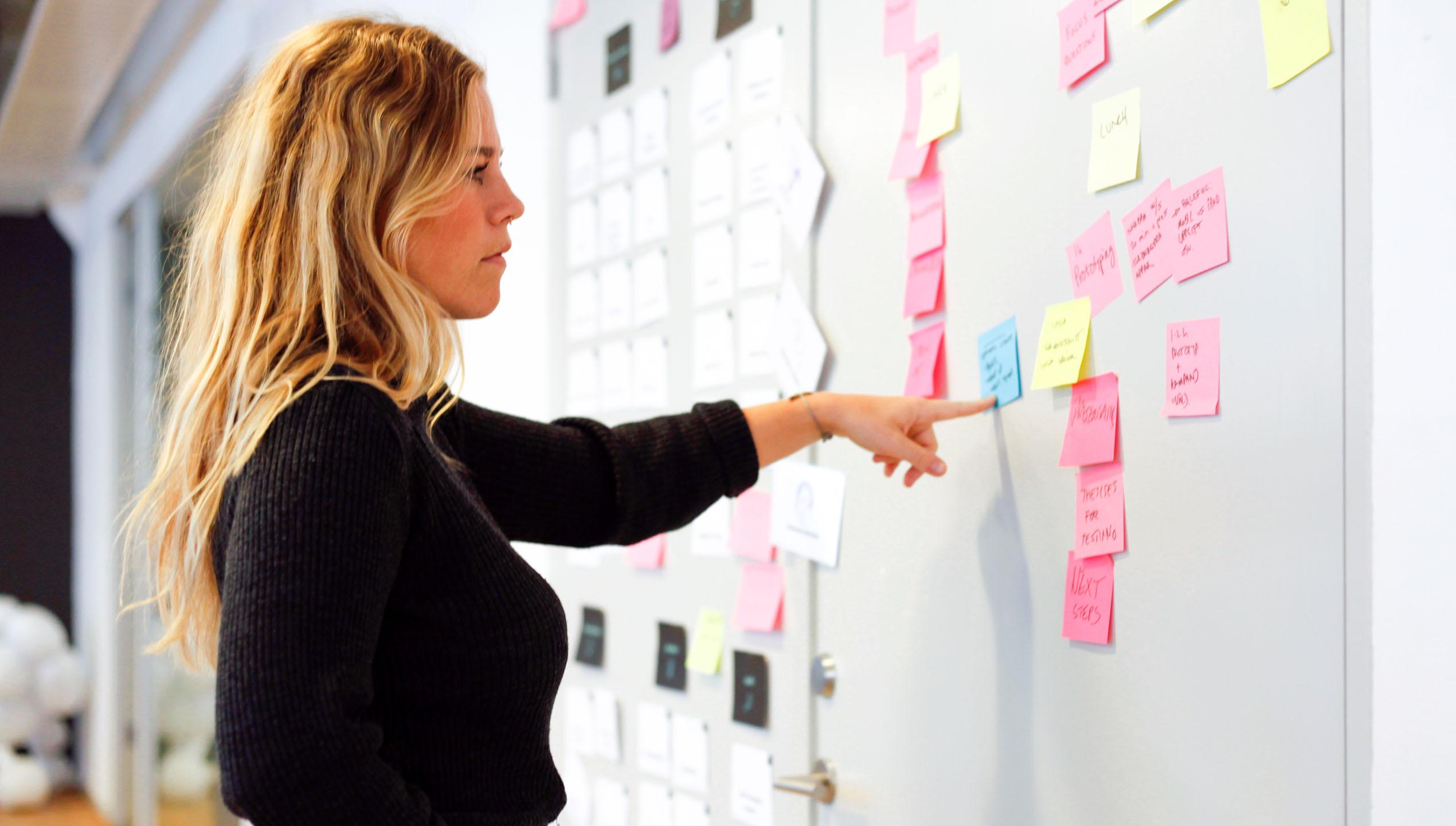 Kvinna som står framför en whiteboard med massor av postat-lappar