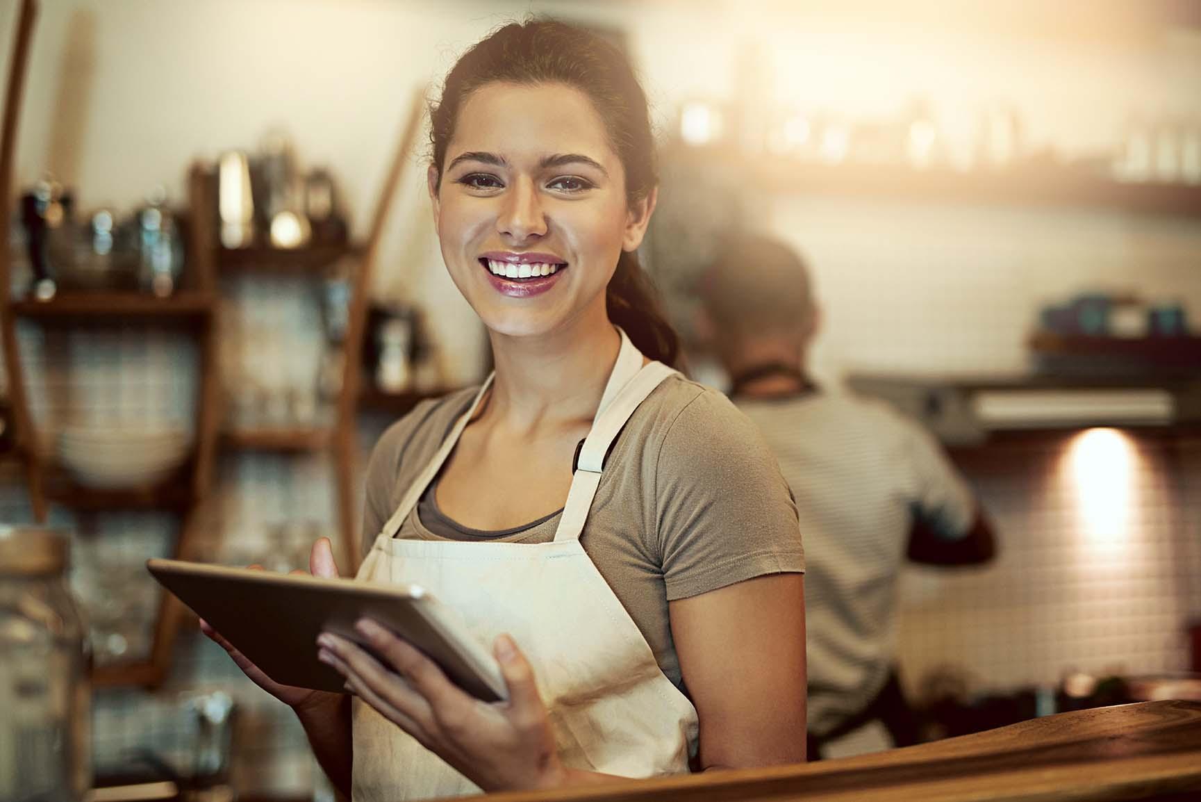 Kvinna står på ett cafe med en iPad i handen